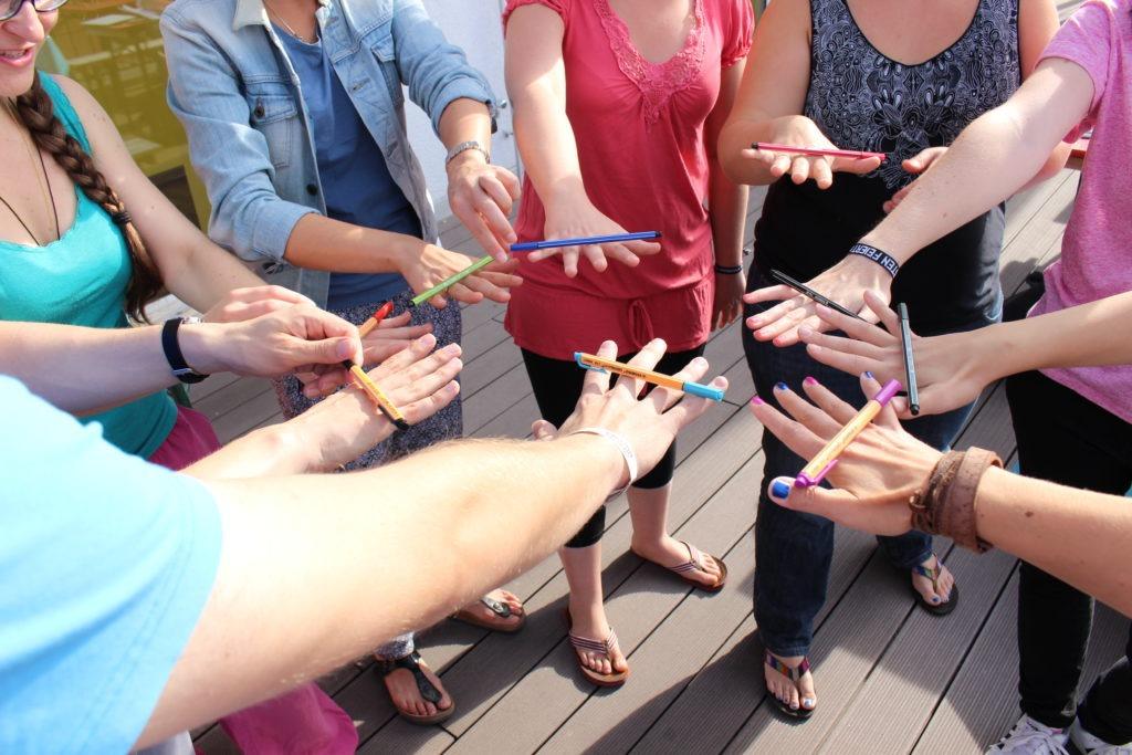 Eine Gruppe Jugendlicher steht im Kreis und balanciert Stifte.