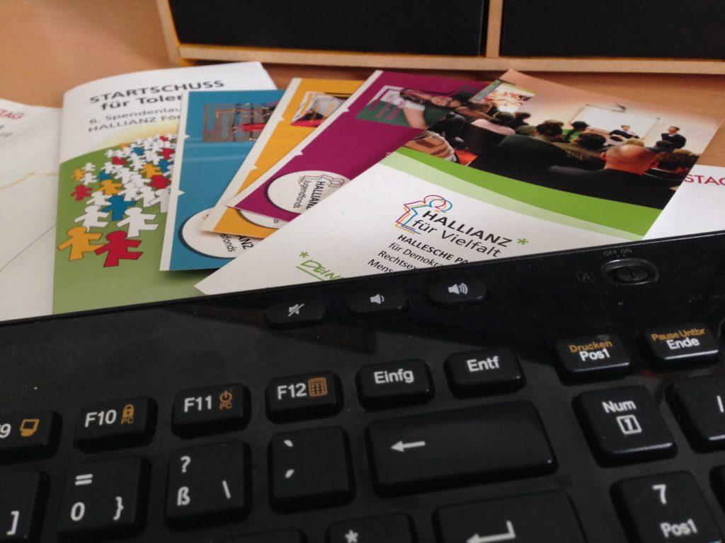 Auf einem Tisch steht eine Tastatur und liegen Flyer.
