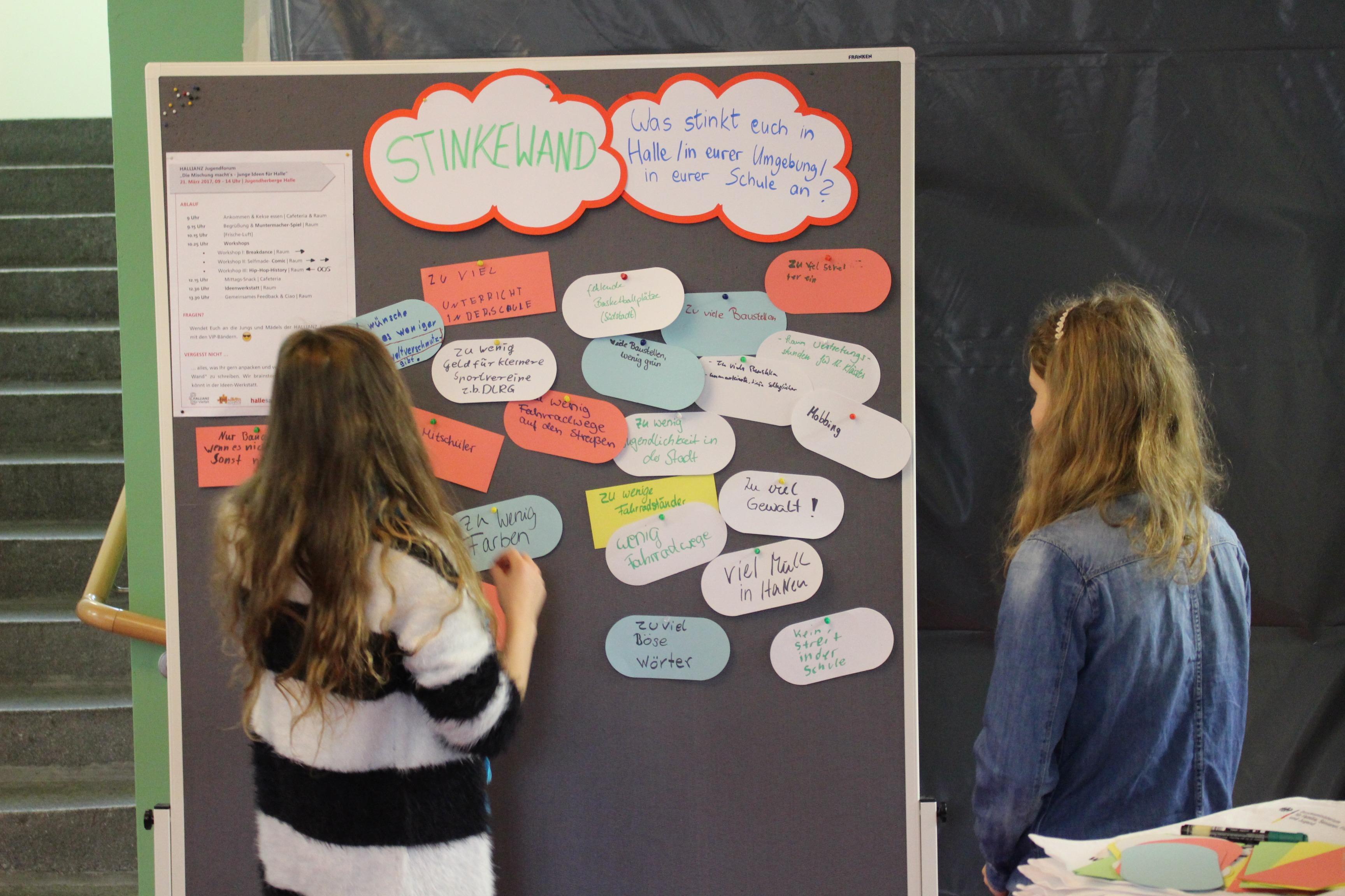 Zwei Jugendliche stehen vor einer Pinnwand.