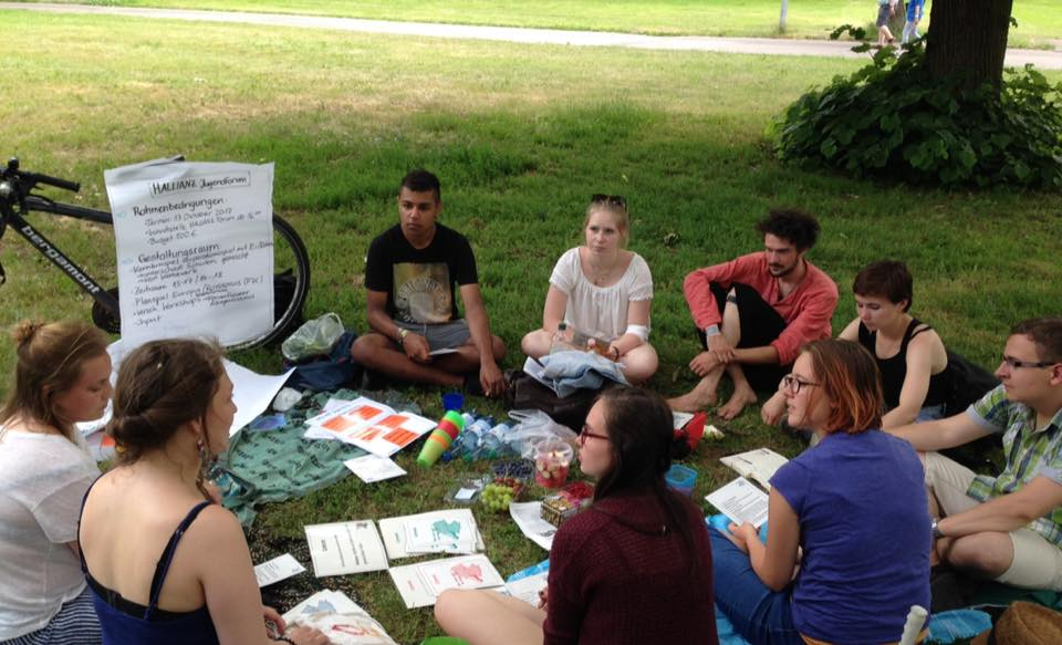 Eine Gruppe Jugendlicher sitzt auf der Wiese und hört einem Vortrag zu.