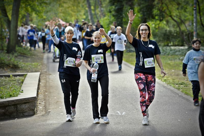 Drei Läuferinnen winken in die Kamera.