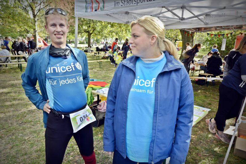 Zwei Menschen mit blauer Kleidung von UNICEF stehen auf einer Wiese.
